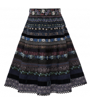 The classic ribbon skirt by Lena Hoschek made from patterned and embroidered ribbons featuring alpine flower patterns. The skirt has a fitted waistband and a flared A-line shape. Side zip fastening.