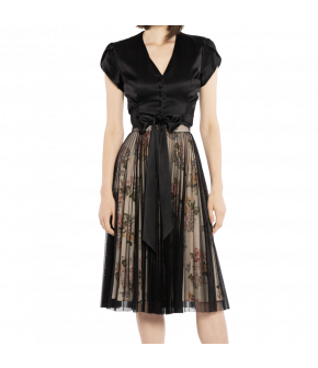 Under the black pleated mesh skirt, an underskirt in a sweet floral pattern shows through. This flared skirt has hidden side pockets and a waistband that closes at the back with a zipper and button.