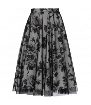 Floral print skirt with an overlay of black tulle. The swing skirt features hidden side pockets. It closes at the side with a zipper and button.