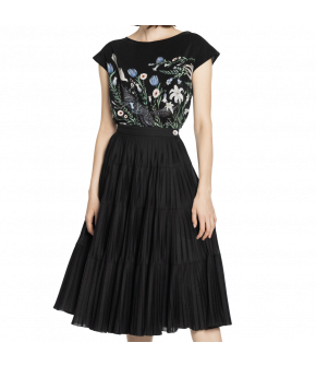 This flared black skirt is pleated and sits at the waist. It closes at the back with a zipper and button.